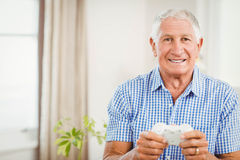 Senior man holding joystick and looking at camera Stock Photos