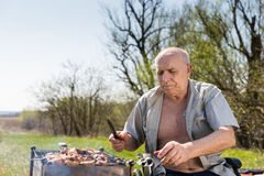 Senior Man Holding Knife While Grilling Outside Royalty Free Stock Photo