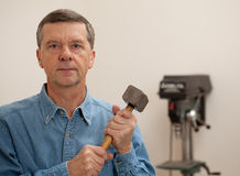 Senior man holding a large hammer Stock Photography