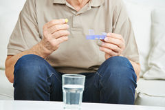 Senior man holding medication. In his hand Stock Photos