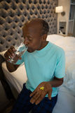 Senior man holding medicine while drinking water in bedroom. At home Royalty Free Stock Photo