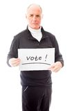 Senior man holding a message board with the text words Vote Stock Image