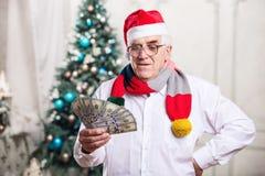 Senior man holding money on Christmas background Stock Images