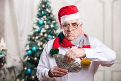 Senior man holding money on Christmas background Stock Images