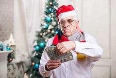 Senior man holding money on Christmas background Royalty Free Stock Photos