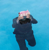 Senior man holding piggy bank above water. Senior caucasian man holding piggy bank above water as he slowly drowns in debt wearing business suit Royalty Free Stock Images