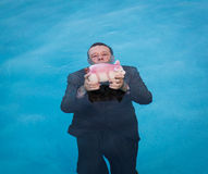 Senior man holding piggy bank above water. Senior caucasian man holding piggy bank above water as he slowly drowns in debt wearing business suit Royalty Free Stock Photography