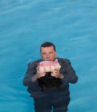 Senior man holding piggy bank above water. Senior caucasian man holding piggy bank above water as he slowly drowns in debt wearing business suit Stock Images