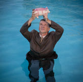 Senior man holding piggy bank above water. Senior caucasian man holding piggy bank above water as he slowly drowns in debt wearing business suit Royalty Free Stock Photos