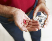 Senior man holding pills Stock Photo