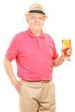 Senior man holding a pint of beer Royalty Free Stock Photos