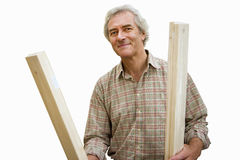 Senior man holding planks of wood, cut out stock images
