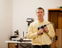 Senior man holding power drill. Senior male in a home workshop facing the camera and holding a power drill Stock Photography