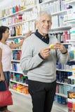 Senior Man Holding Product While Female Shopping In Pharmacy Stock Image