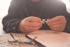Business senior man assembling pieces of a puzzle royalty free stock photos