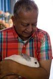 Senior man holding rabbit at retirement home. Close up senior man holding rabbit at retirement home Stock Photography