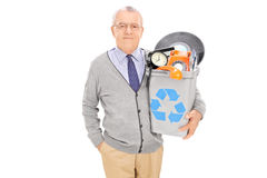 Senior man holding a recycle bin full of old stuff Stock Photography