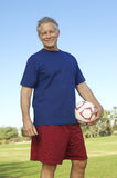 Senior Man Holding Soccer Ball At Park Stock Photo