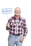 Senior man holding a social media sign smiling Stock Photo