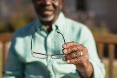 Senior man holding spectacle in the park of nursing home. Mid section of senior African-American man holding spectacle in the park of nursing home stock photography