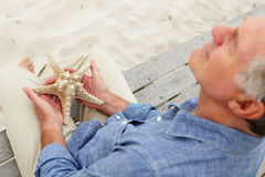 Senior man holding starfish Royalty Free Stock Images