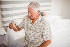 Senior man holding a thermometer Stock Photography