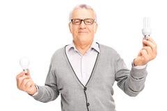 Senior man holding two light bulbs Stock Photo