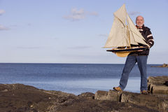 Senior man holding up model sailboat by sea, smiling, portrait Stock Images