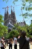Elderly tourist taking photo of the cathedral La Sagrada Familia stock photography