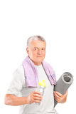 Senior man holding a water bottle and an exercise mat Royalty Free Stock Photos