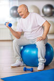 Senior man  holding weights in gym Stock Images