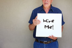Senior man holding white canvas board in front of his face with the phrase hire me! Stock Image