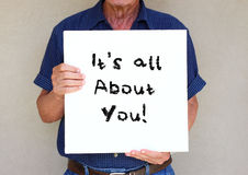 Senior man holding white canvas board in front of his face with the phrase it's all about you Stock Image