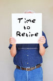 Senior man holding white canvas board in front of his face with the phrase time to retire.  Royalty Free Stock Image