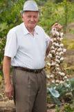 Senior man holding a wreath of garlic Royalty Free Stock Photos