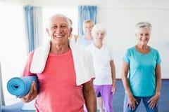 Senior man holding yoga mat. Senior men holding yoga mat during sports class stock photography