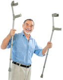 Senior man holds the crutches. Smiling. isolated on white background Royalty Free Stock Image