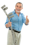 Senior man holds the crutches. Senior man holding the crutches smiling. Concept for recovering Royalty Free Stock Image