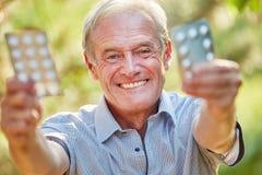 Senior man holds medicament with joy Royalty Free Stock Image