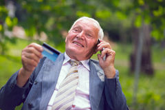 Senior man holds out a credit card cu laughs Royalty Free Stock Photography