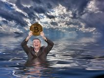 Senior Man Holds Up Bitcoin And Drowns In Ocean Stock Image