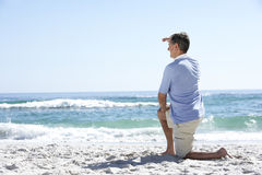 Senior Man On Holiday Kneeling On Sandy Beach Royalty Free Stock Photo