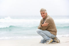 Senior Man On Holiday Kneeling On Winter Beach. Smiling At Camera Royalty Free Stock Images