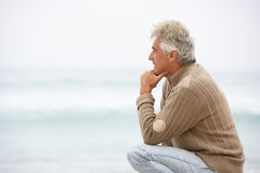 Senior Man On Holiday Kneeling On Winter Beach. Looking At Sea Royalty Free Stock Photography