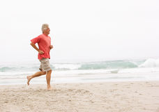Senior Man On Holiday Running Along Beach. Senior Man On Holiday Running Along Winter Beach Royalty Free Stock Image