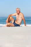 Senior Man On Holiday Sitting On Beach Stock Photo