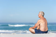 Senior Man On Holiday Sitting On Sandy Beach Royalty Free Stock Image