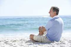 Senior Man On Holiday Sitting On Sandy Beach Stock Images