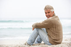 Senior Man On Holiday Sitting On Winter Beach. Smiling At Camera Stock Images