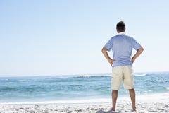 Senior Man On Holiday Standing On Sandy Beach Stock Image